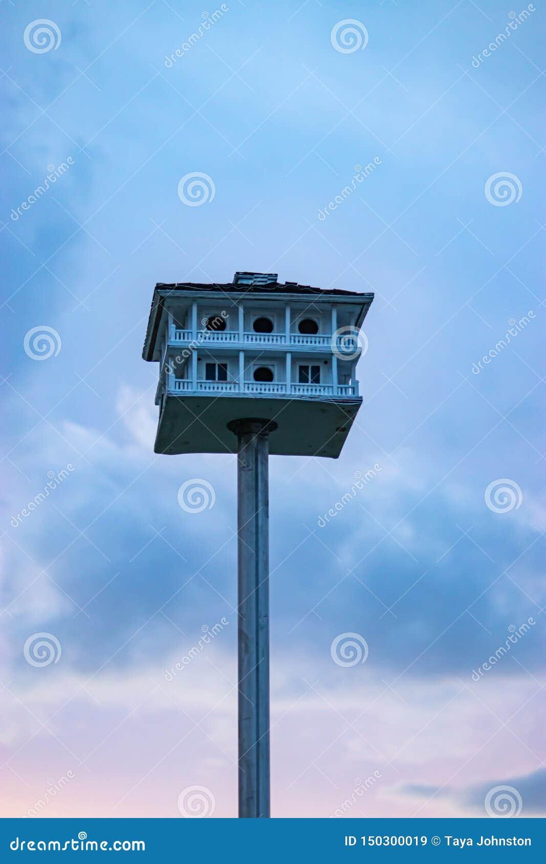Een oude hand bewerkte vogelhuis met pilars en een omslag rond dek op een metaalpool