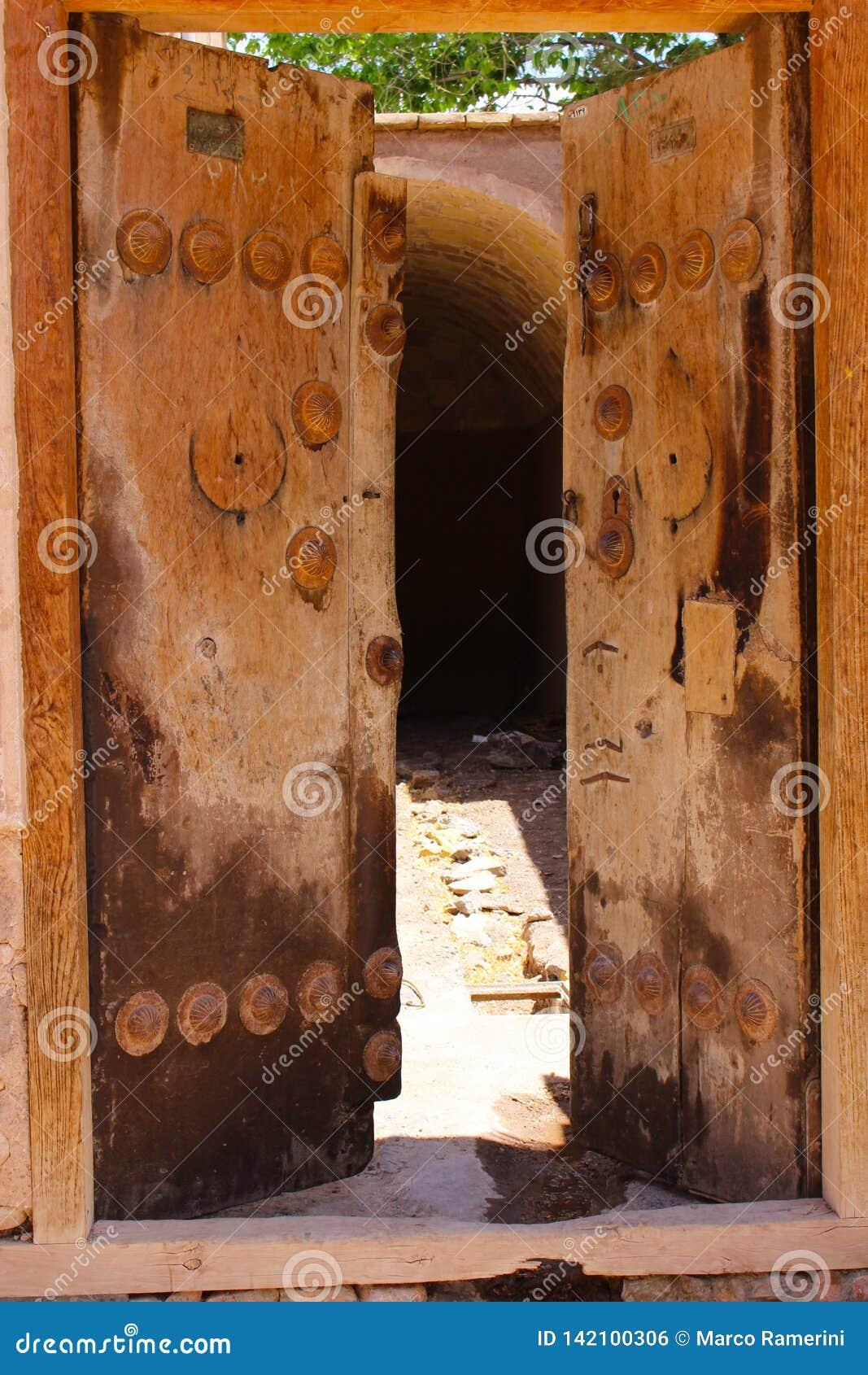 Een oude houten deur in de stad van Rayen, Iran