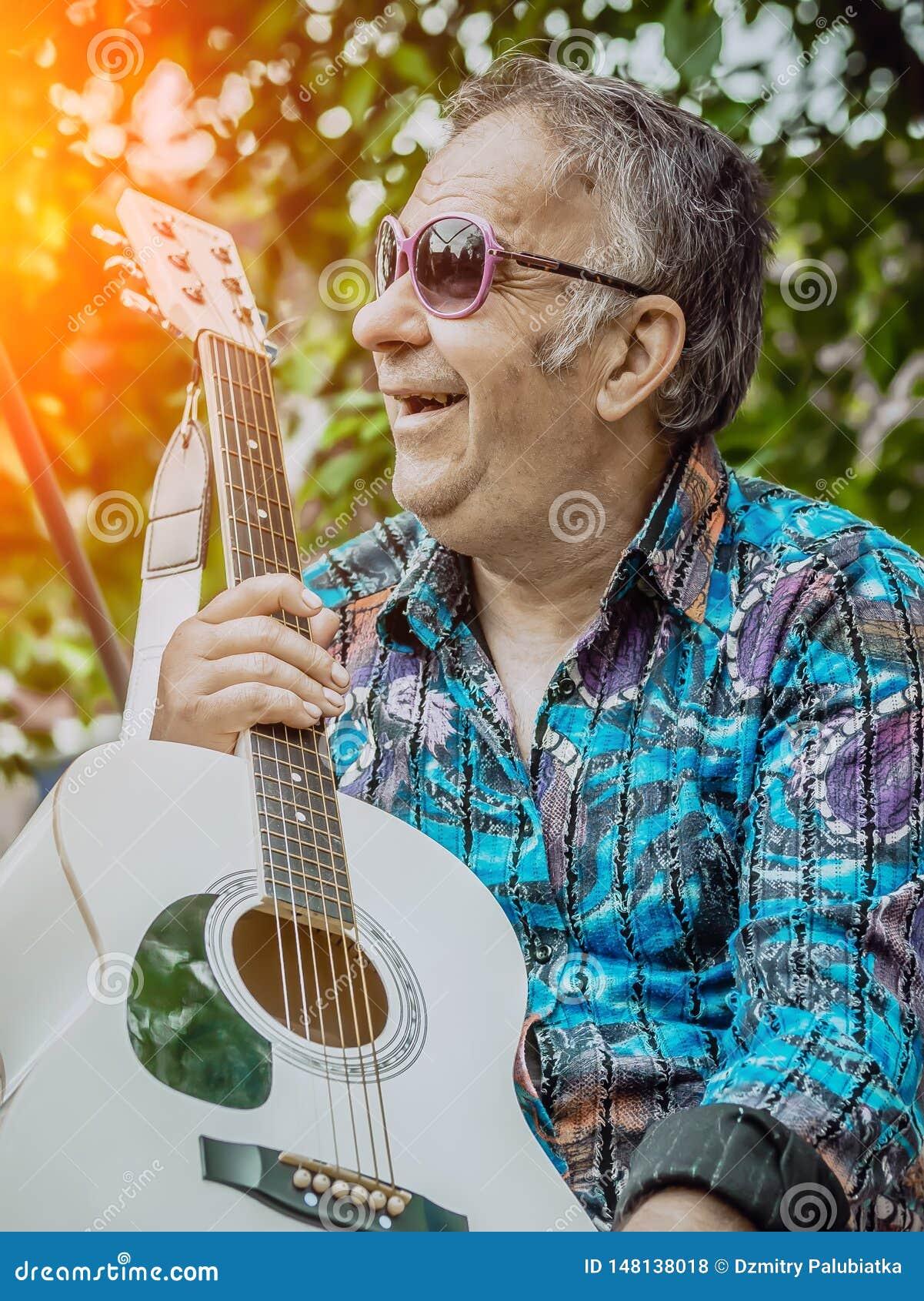 Een oude mens met een gitaar geniet van het leven