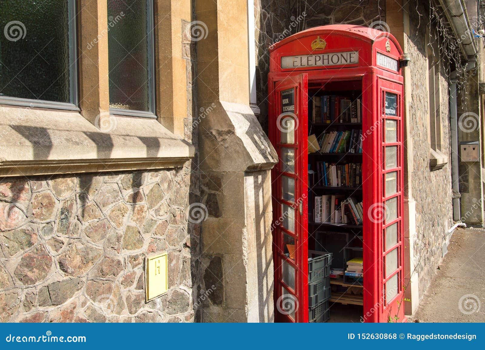 Een oude rode die telefooncel, als communautaire bibliotheek, Malvern, Worcestershire, het UK wordt gebruikt