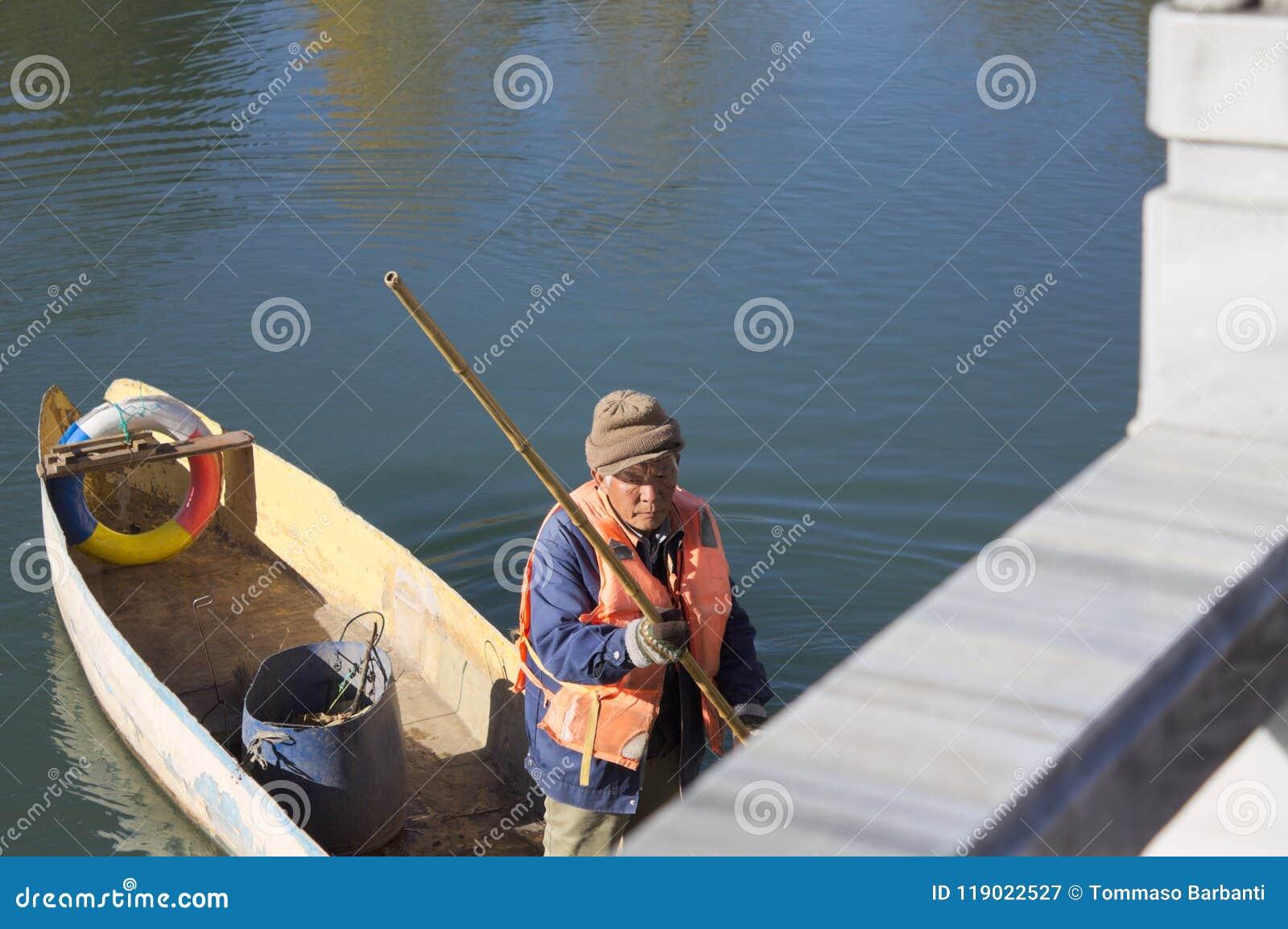 Een oude visser op een houten boot in Zwart Dragon Pool