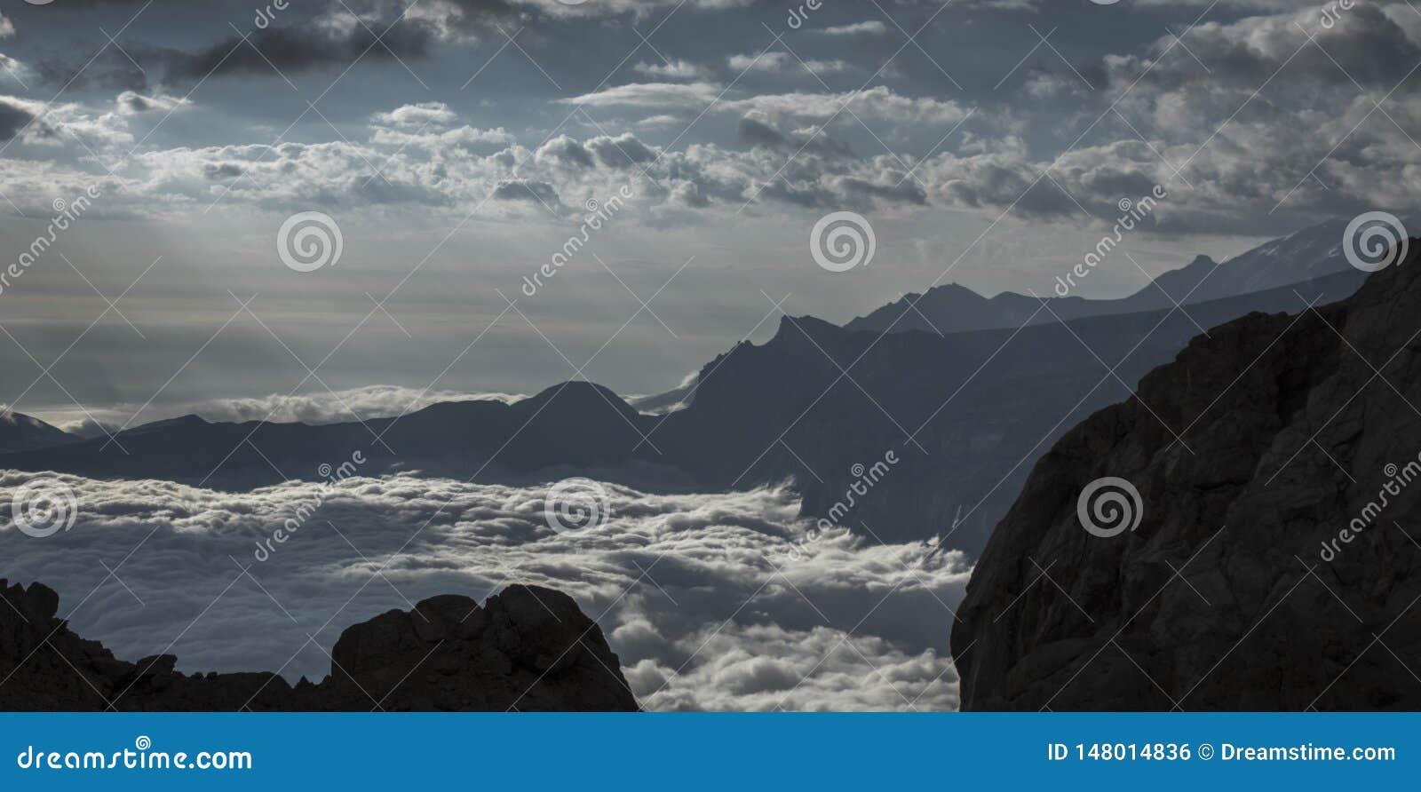 Een overzees van wolken verfraait bergen
