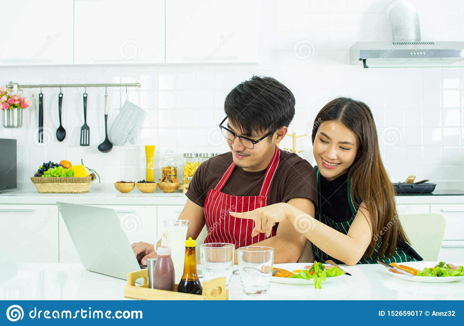 Een paar gebruikt laptop terwijl het hebben van ontbijt in de keuken