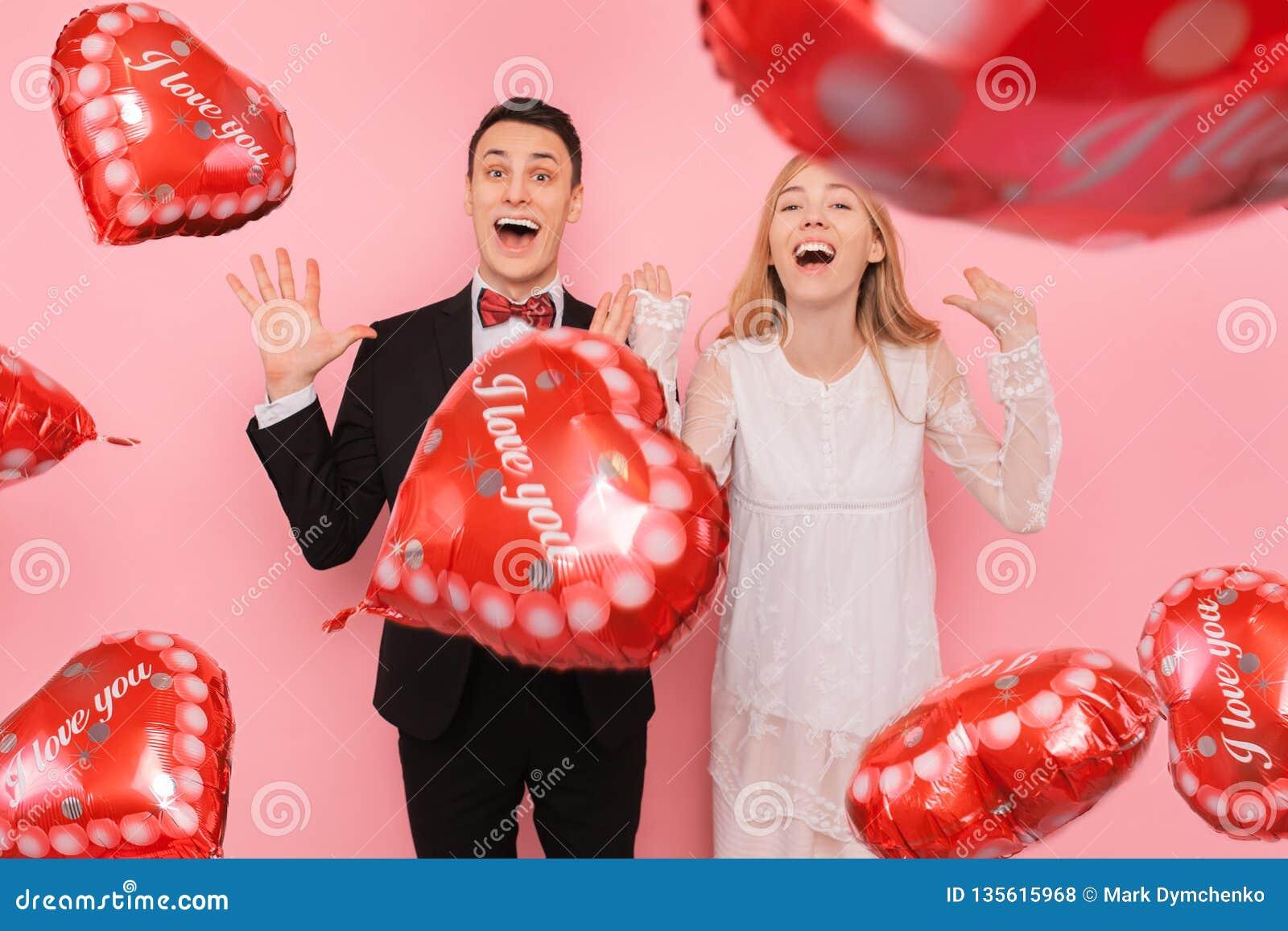 Een paar in liefde, een man en een vrouw, die ballons in de vorm van een hart op een roze achtergrond houden, genieten van de dag