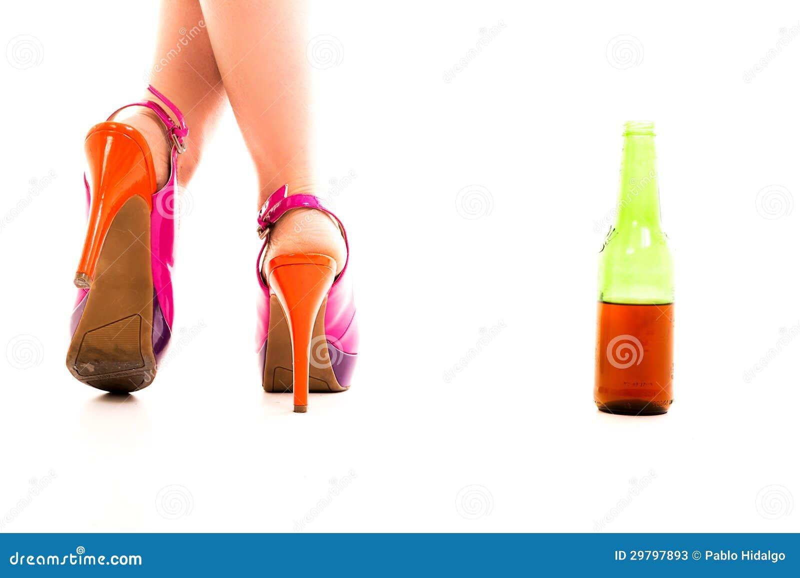 Een paar van rode hielschoenen en een fles bier