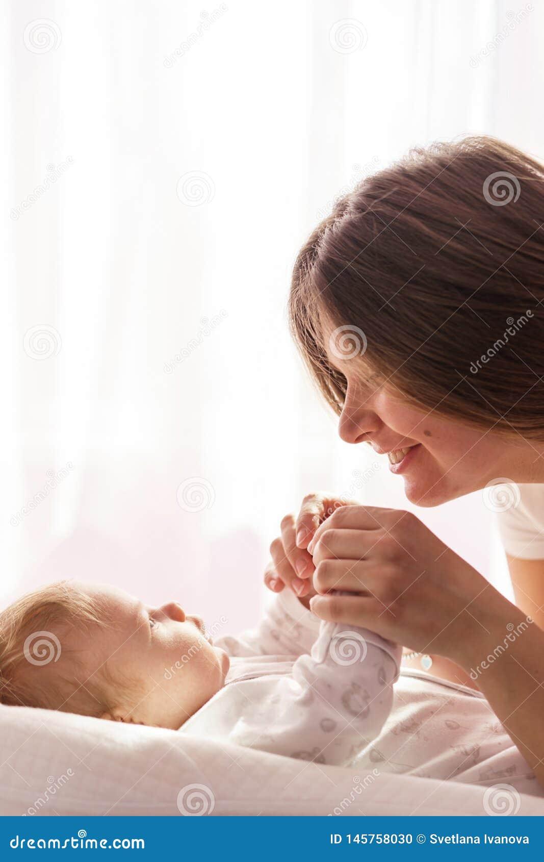 Een pasgeboren baby ligt op het bed en de moeder houdt zijn handen