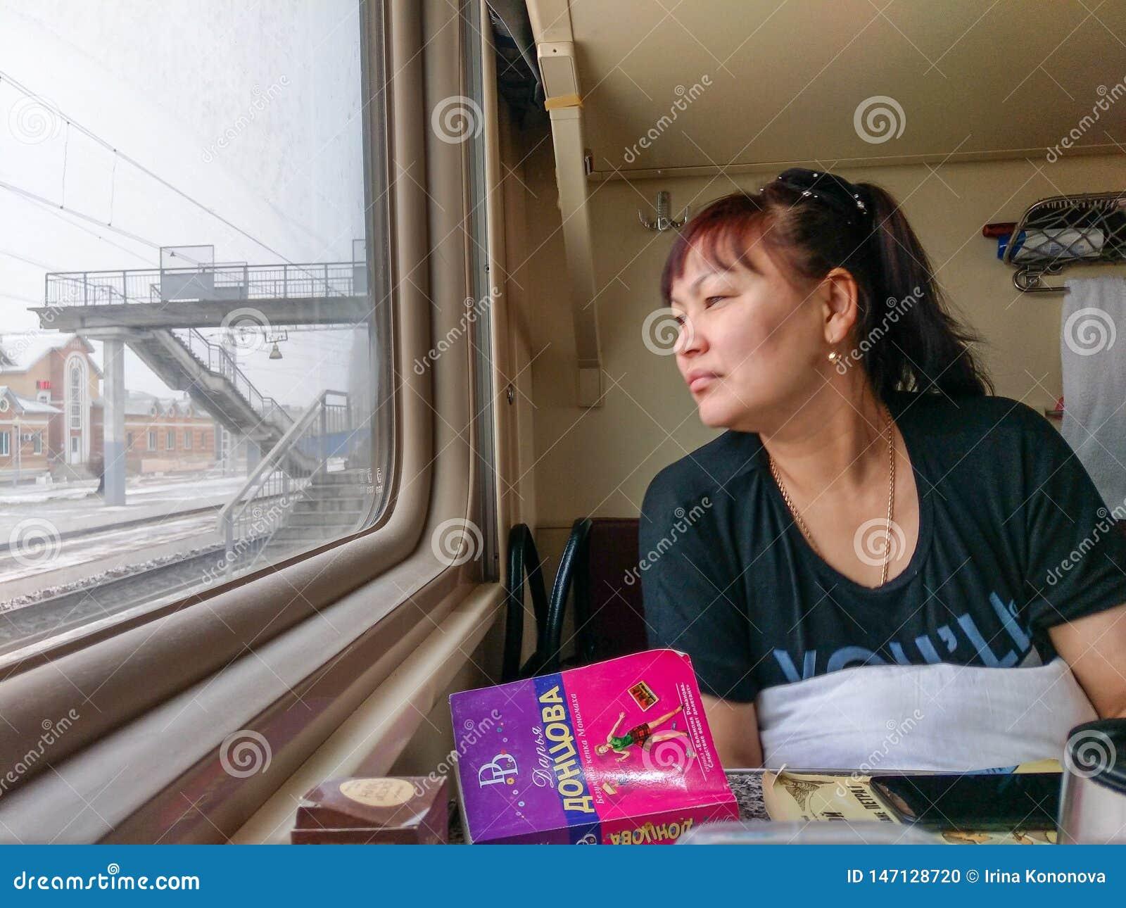 Een passagier reist op een trein Moskou-Vladivostok en kijkt uit het venster