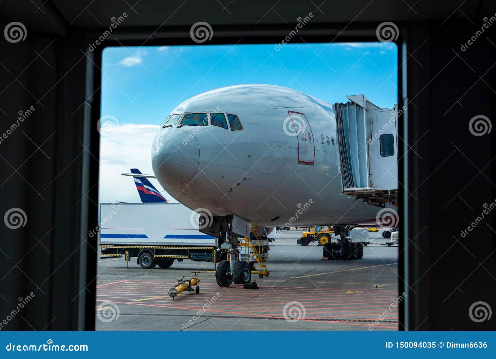 Een passagiersvliegtuig bevindt zich bij de luchthaven in een parkeerplaats die op vertrek, het proces wachten om voorbereidingen