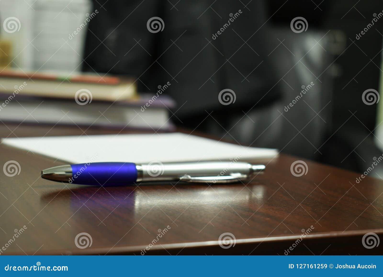 Een pen in de nadruk door het bureau wordt omringd dat