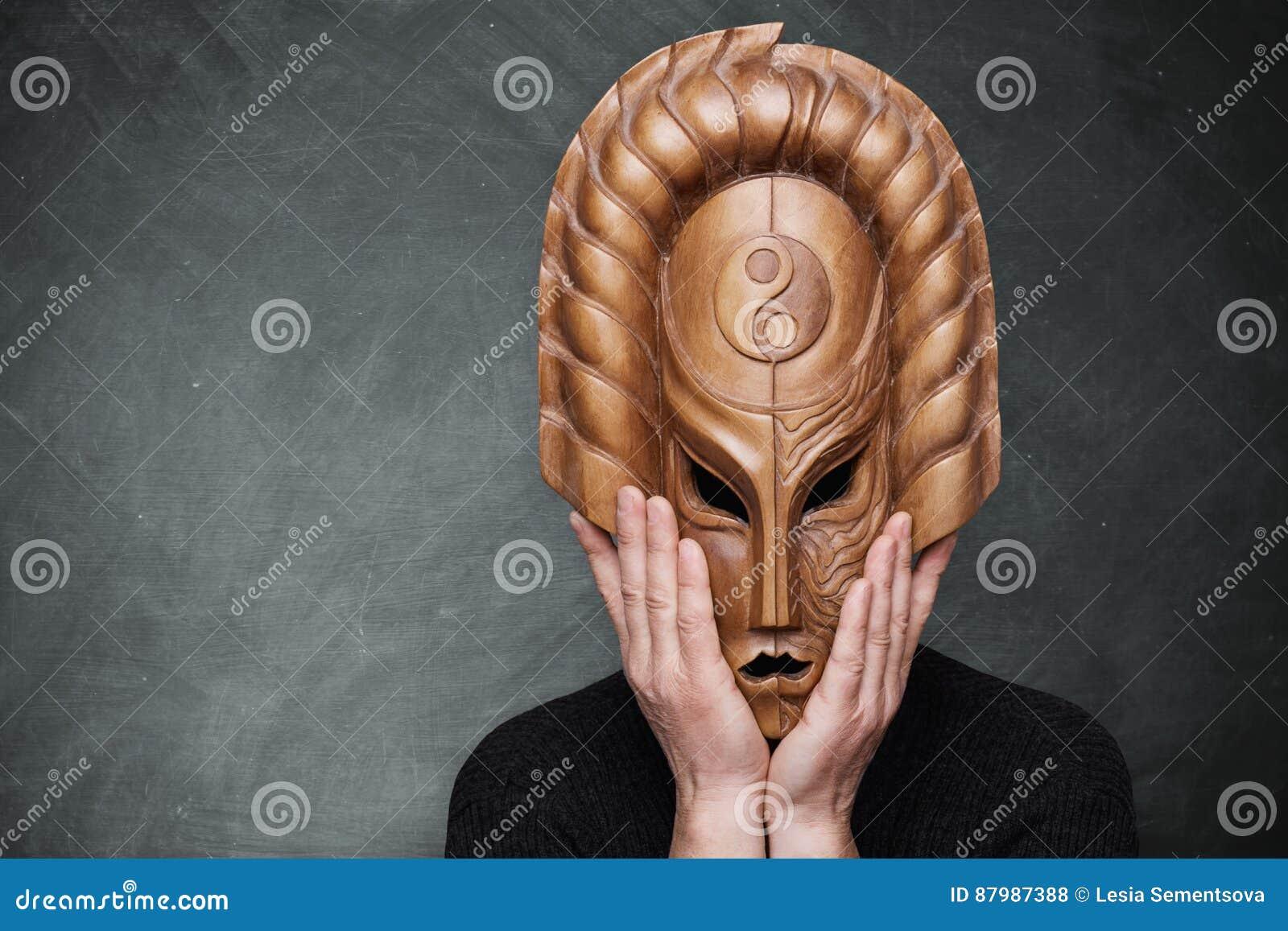Een persoon die houten masker dragen die yin yang harmonie symboliseren die zijn handen op het masker houden die zich over grijze