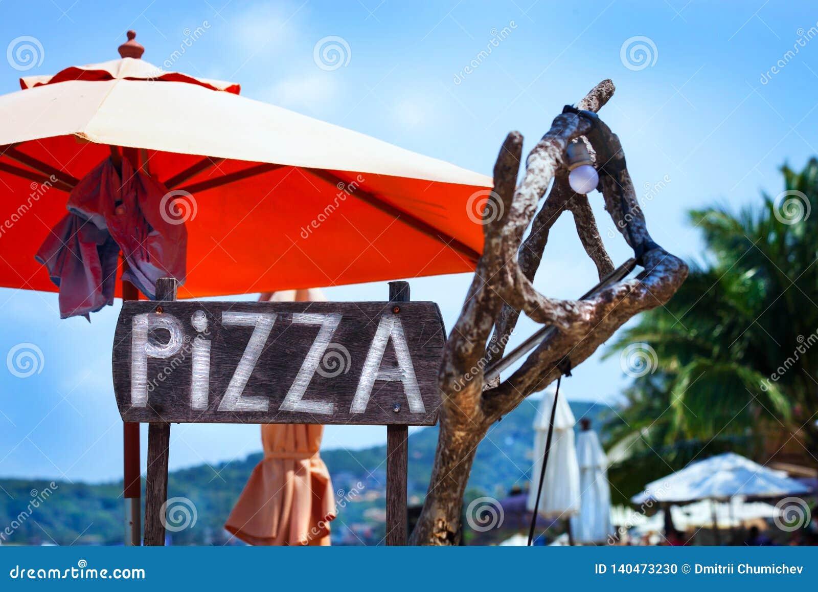 Een Pizza van het reclameteken op het strand