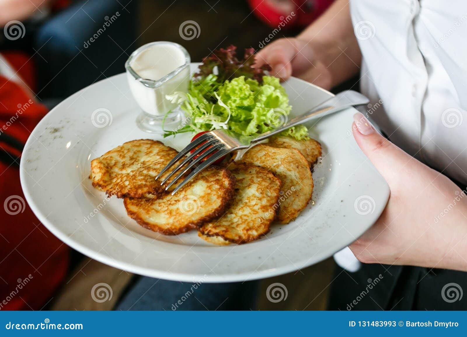 Een plaat van aardappelpannekoeken in de handen van een kelner