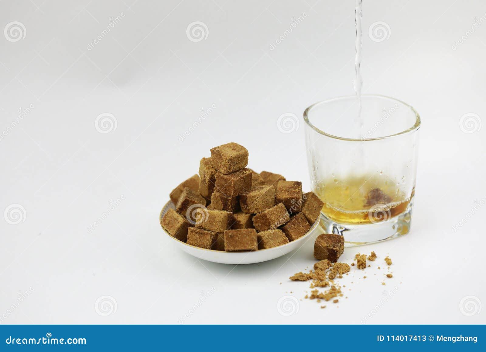 Een plaat van bruine suiker kubeert rotssuiker, bruine suiker in een transparant glas, een stuk van bruine suiker in glas op witt