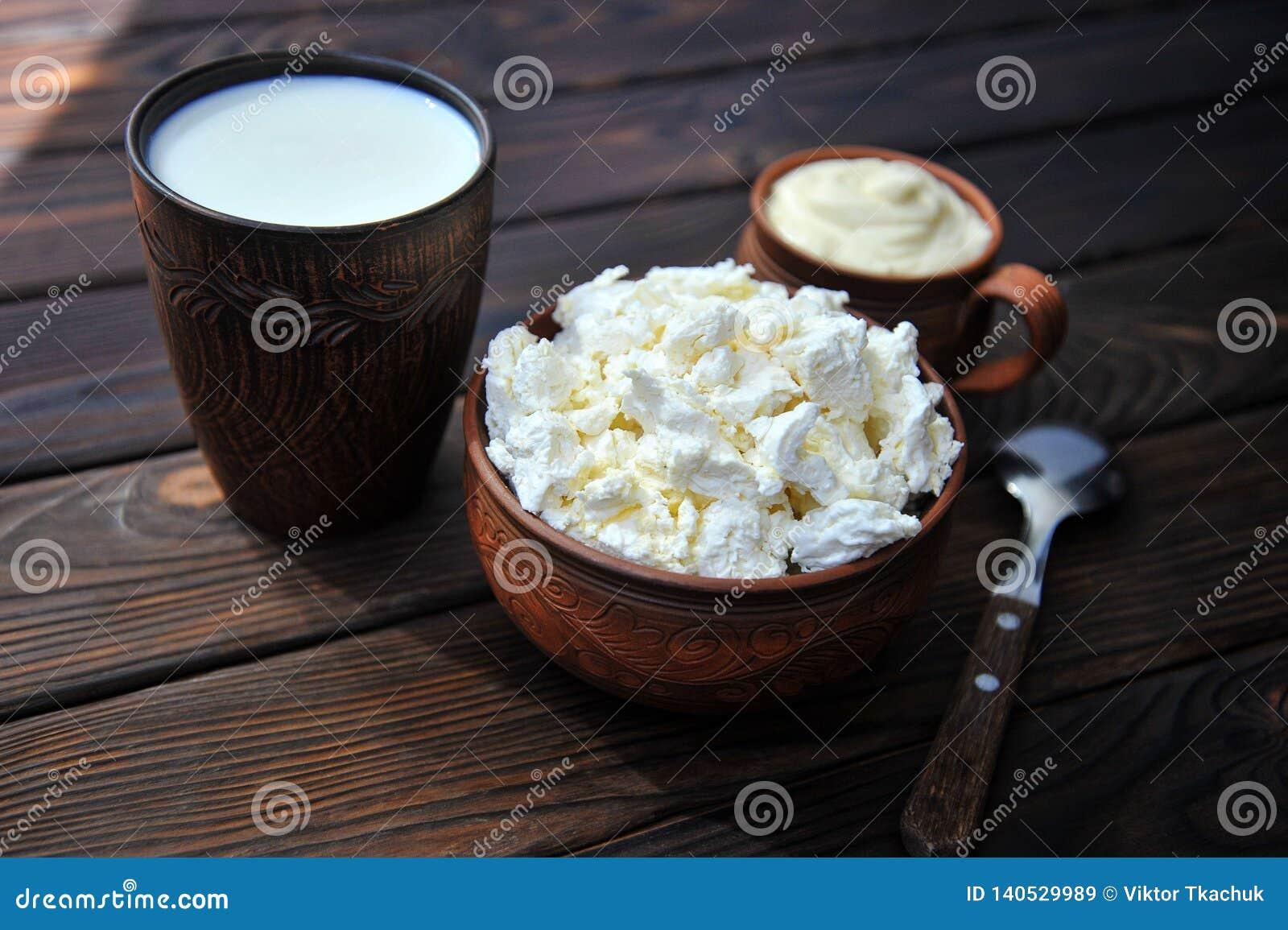 Een plaat van klei met kwark, een mok klei met zure room, een mok met melk en een lepel op a tablen