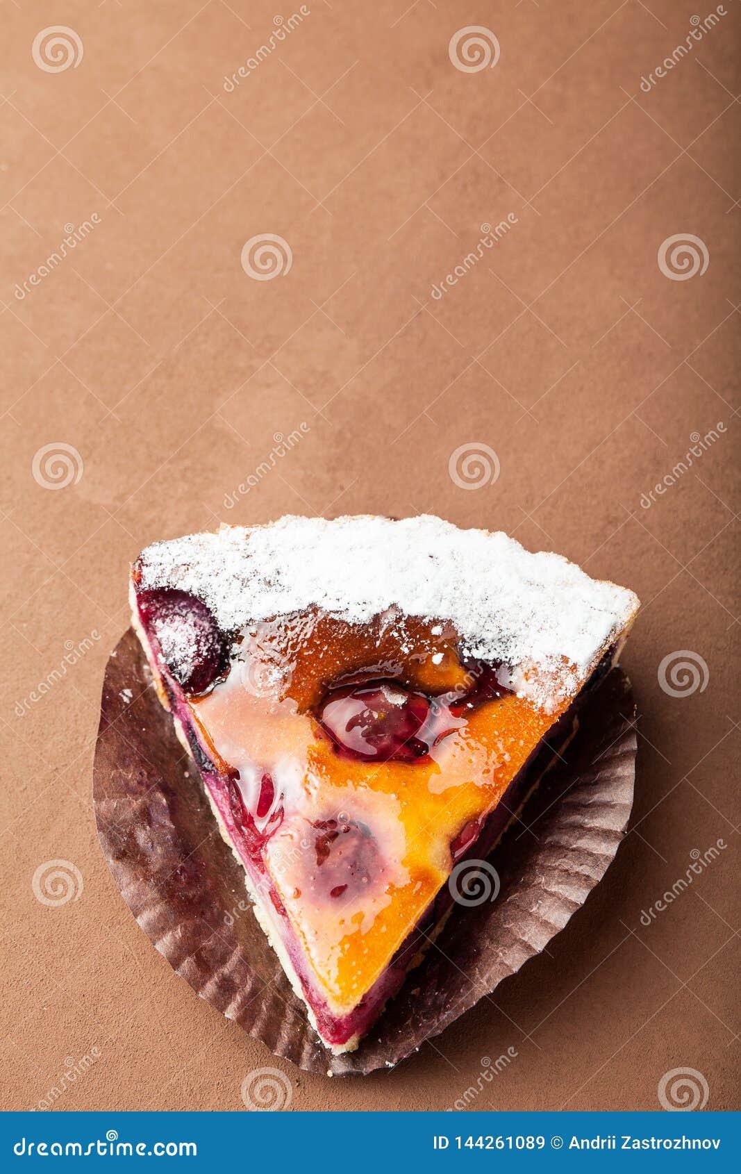 Een plak van zoete dessert of pastei op een bruine achtergrond, lege ruimte voor tekst