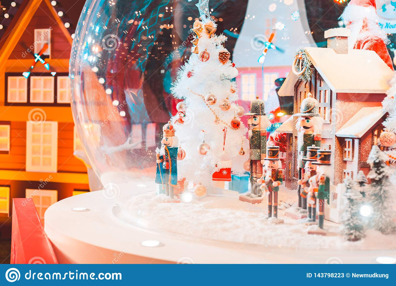 Een een pop en huis van legerkerstmis met sneeuw in de grote glasbal en het licht