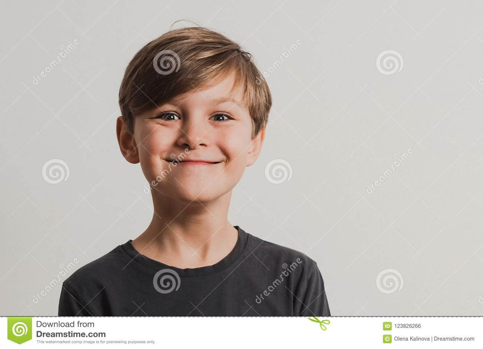 Een portret van leuke jongen die gezichten trekken