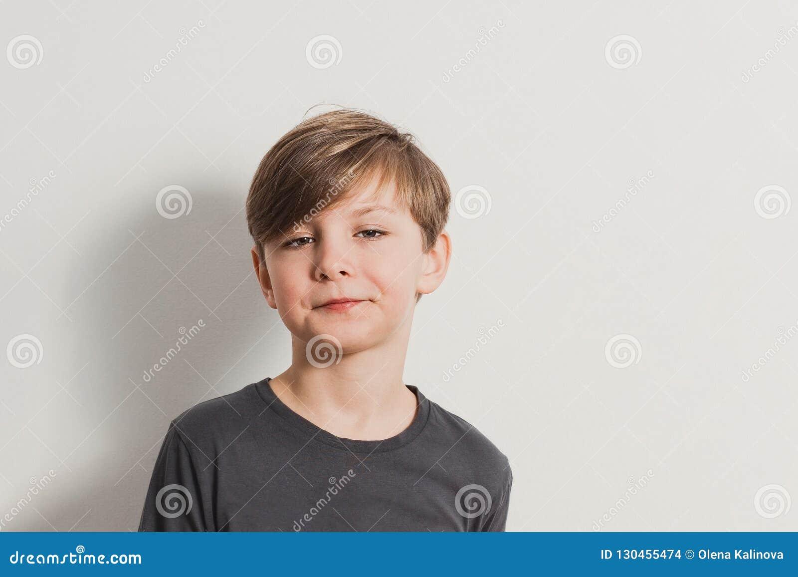 Een portret van leuke jongen die gezichten, verwaande blik trekken