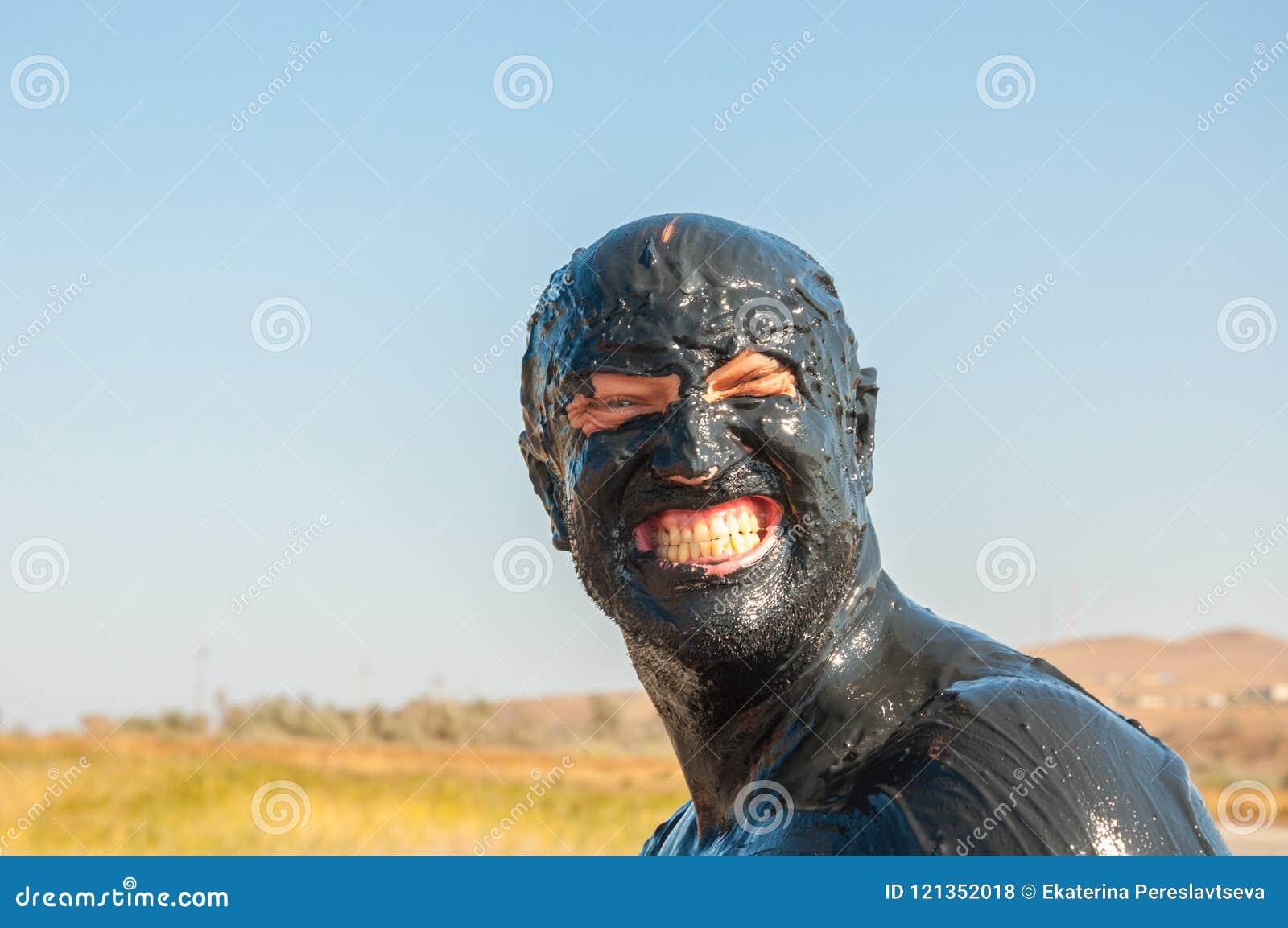 Een portret van een mens in modder en het glimlachen wordt gesmeerd die