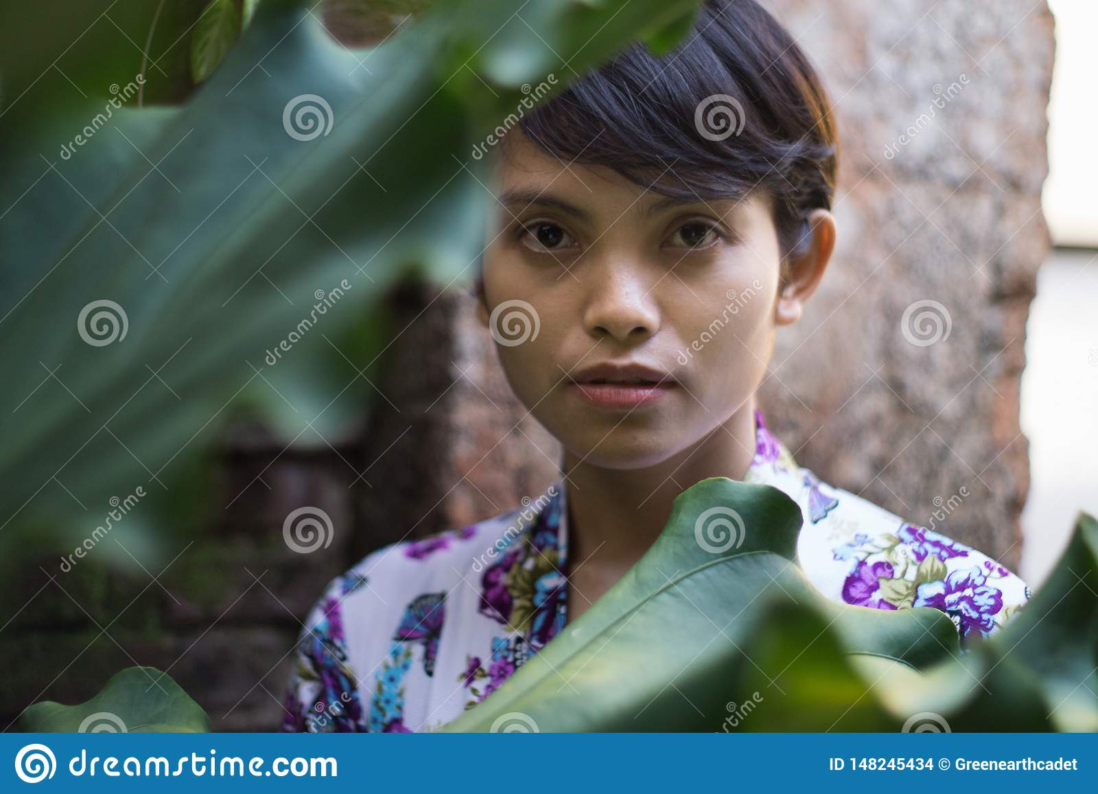 Een portret van een mooie kortharige vrouw met een bloem op zijn oor Zij draagt een kleding van Bali met bloemenmotieven, die ste