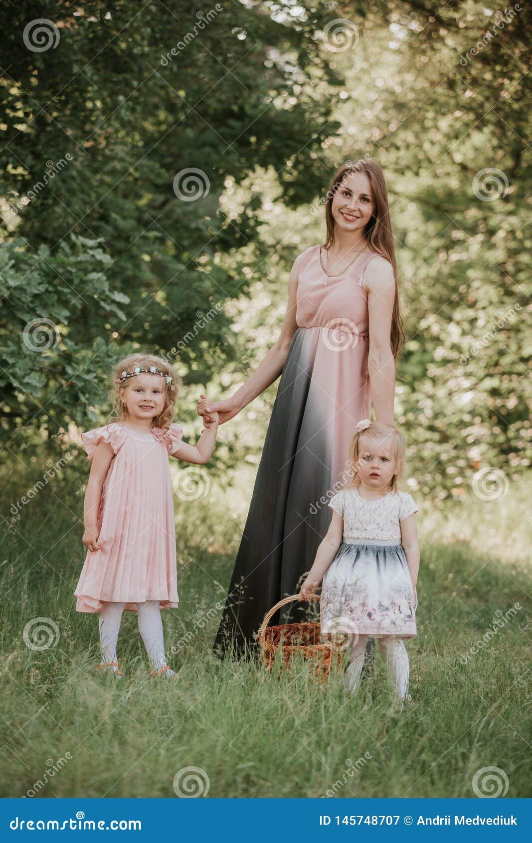 Een prachtig portret van mamma met twee dochters in het park Moeder en twee dochters het wervelen