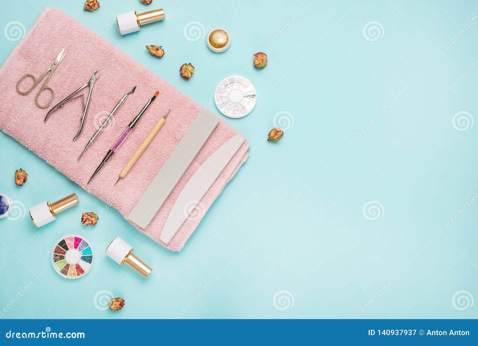 Een reeks kosmetische hulpmiddelen voor manicure en pedicure op een blauwe achtergrond Gelpoetsmiddelen, nagelvijlen en tangen en