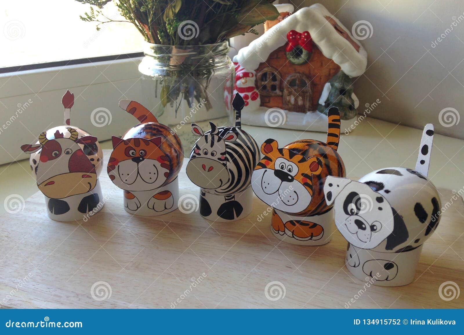 Een reeks paaseieren in de vorm van dieren op houten raad Op de achtergrond een boeket van bloemen in vaas en een huiscijfer