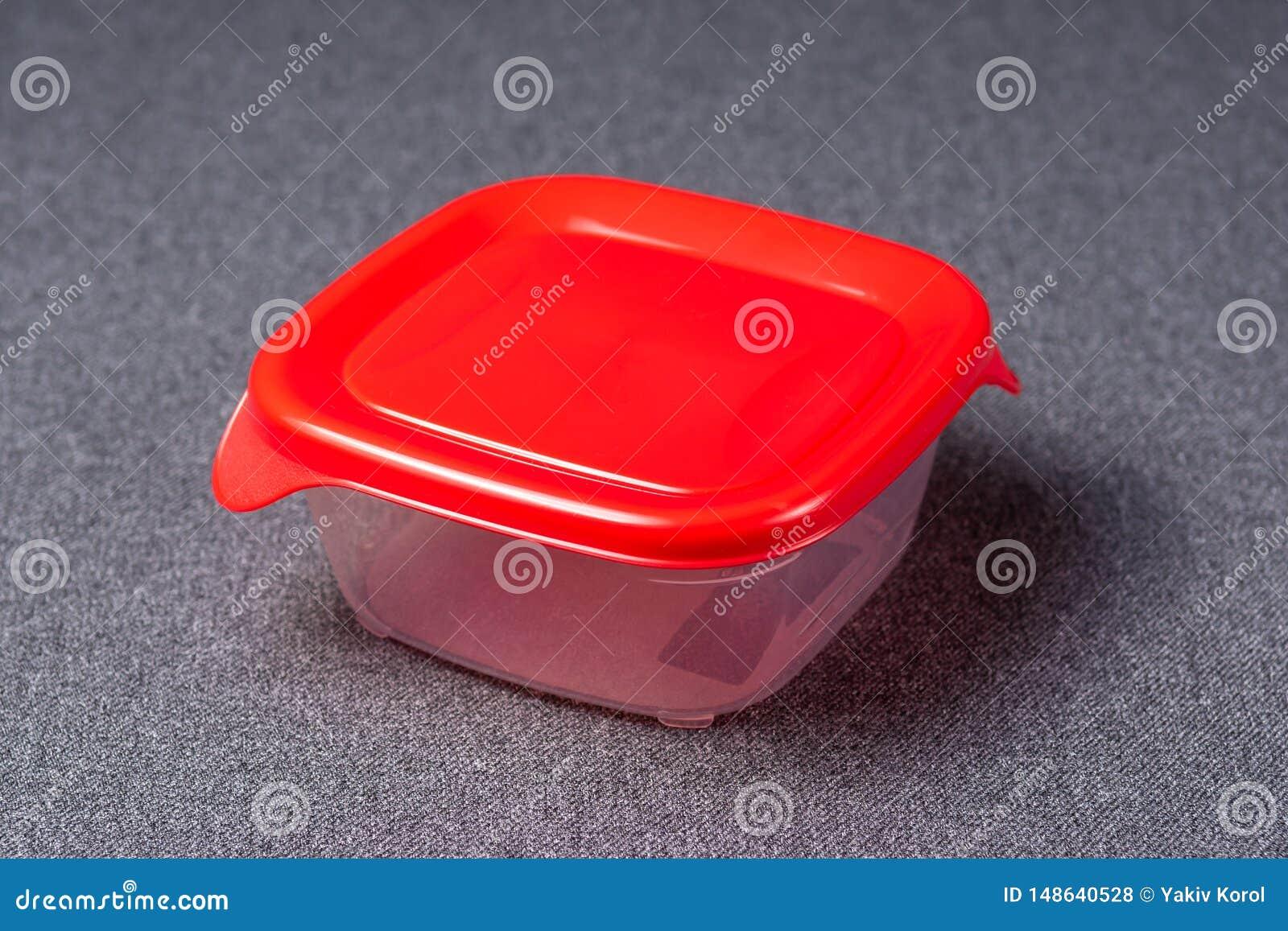 Een reeks plastic werktuigen Plastic koppen, platen, vorken, lepels en plastic containers op een grijze achtergrond Tegen plastie