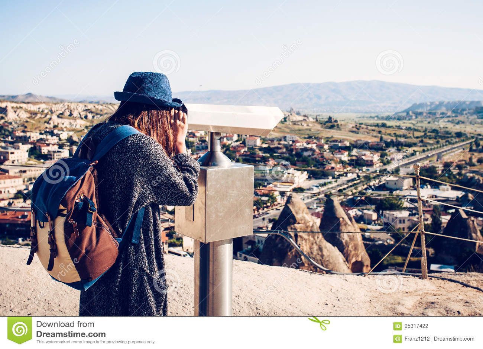 Een reiziger met een rugzak bij gezichtspunt bekijkt binnen door verrekijkers een mooie mening van de stad van Goreme