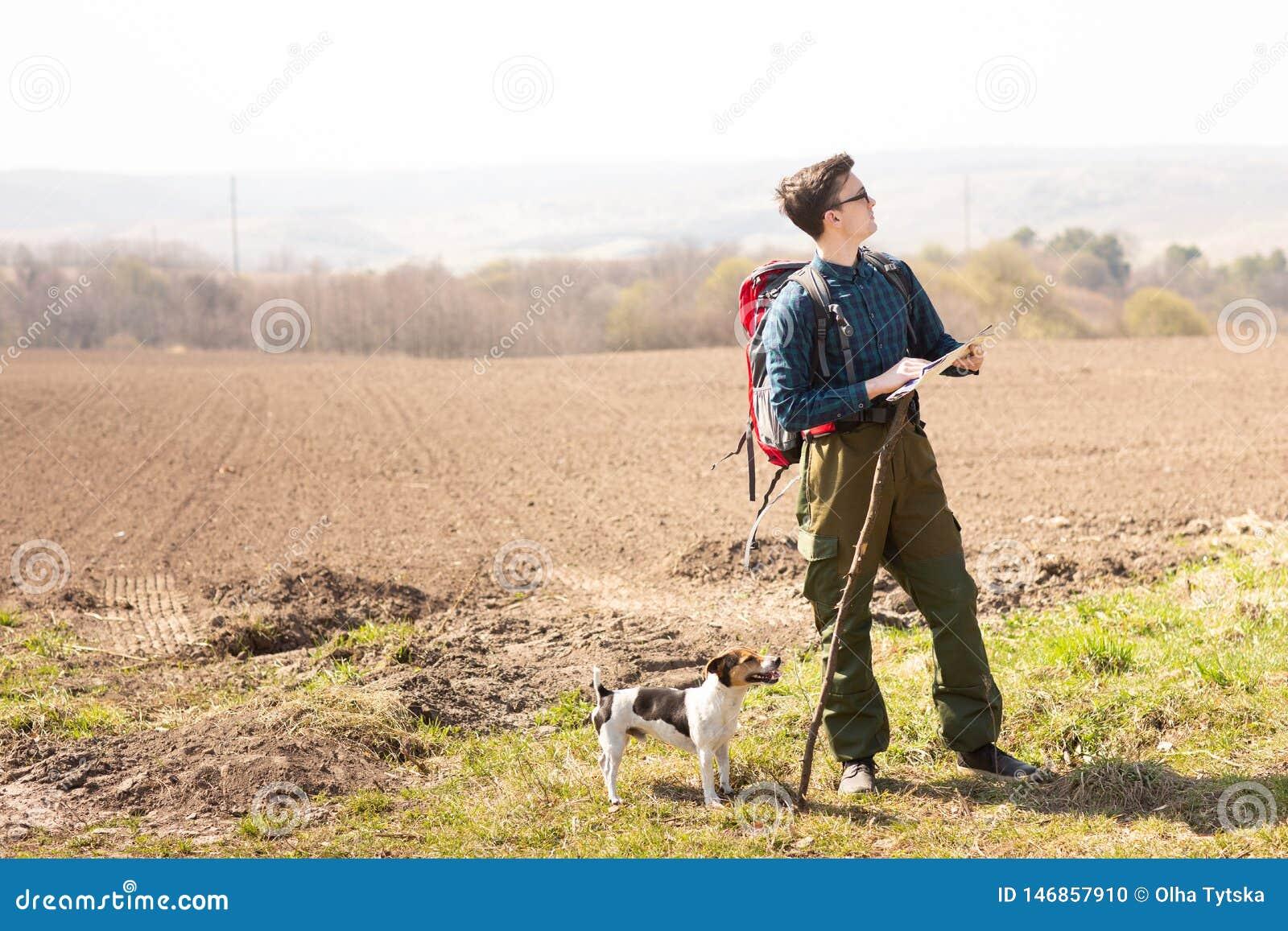 Een reiziger met een rugzak en zijn hond die, die de kaart bekijken en in het platteland lopen