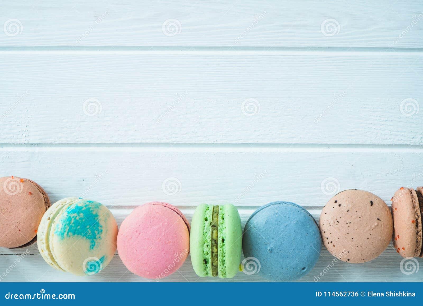 Een rij van multicolored makarons of macaron op een wit houten close-up als achtergrond, amandelkoekjes op een lijst, exemplaarru