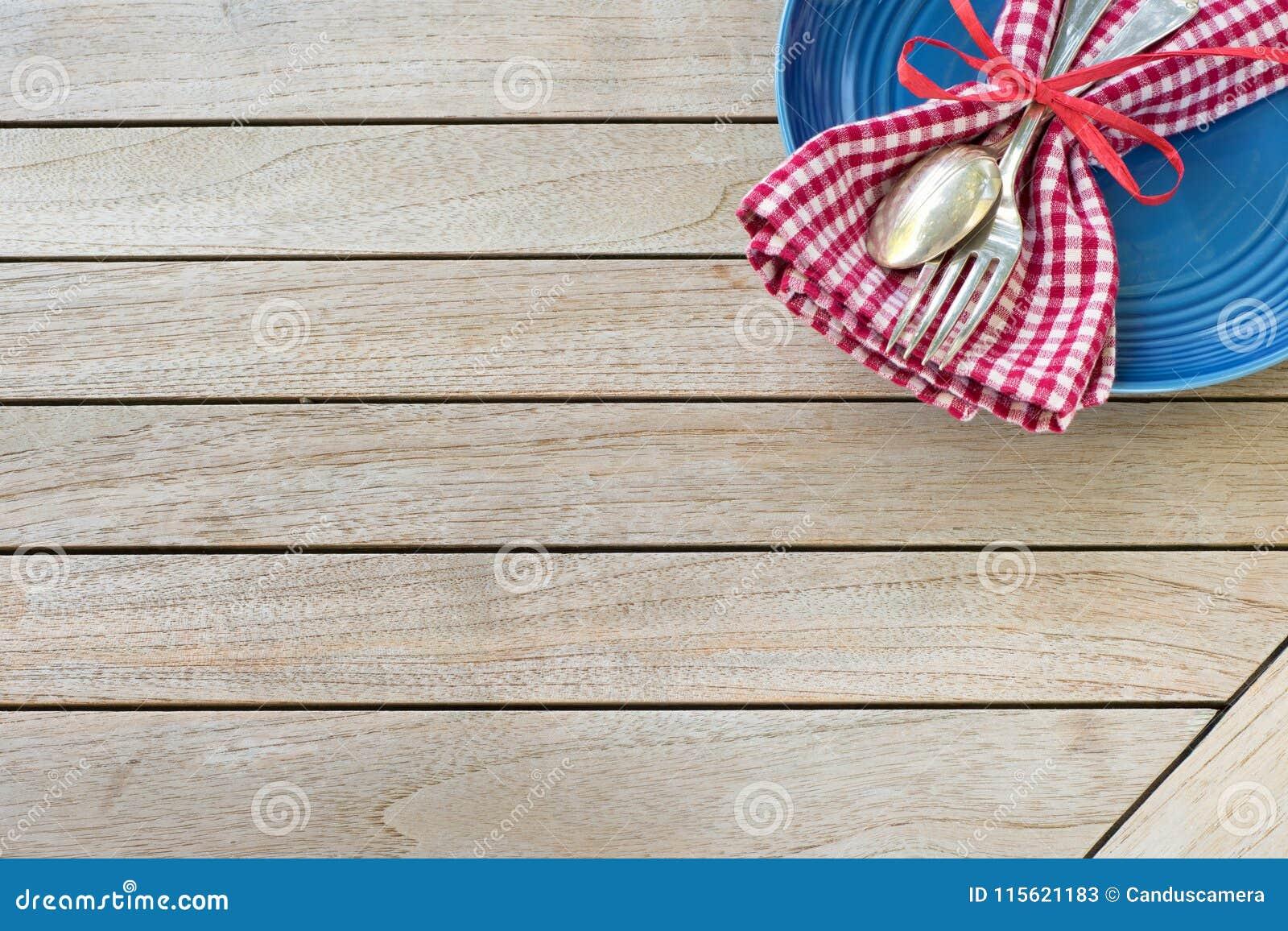 Een Rode Witte en Blauwe Plaats die van de Picknicklijst met servet, vork en lepel en plaat in een hogere hoek op horizontale hou