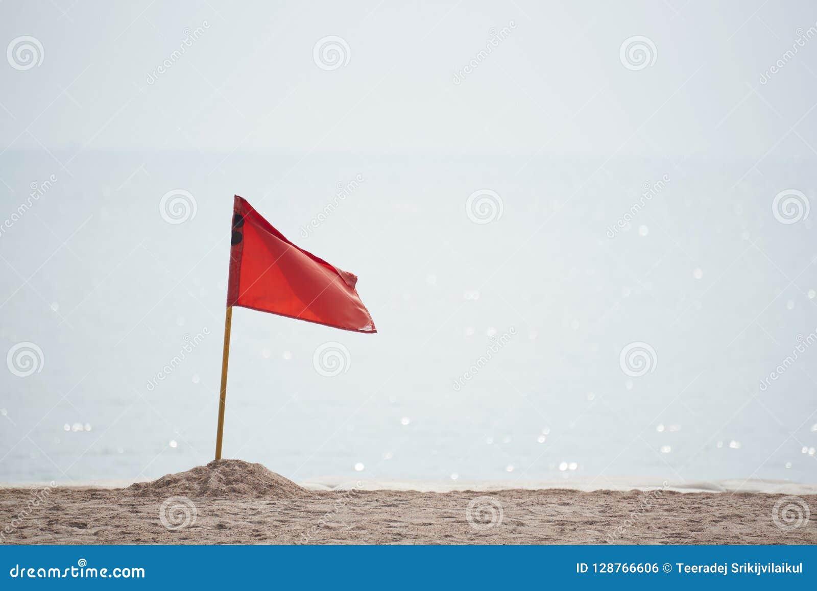 Een rood gevaar van de vlagwaarschuwing op het strand