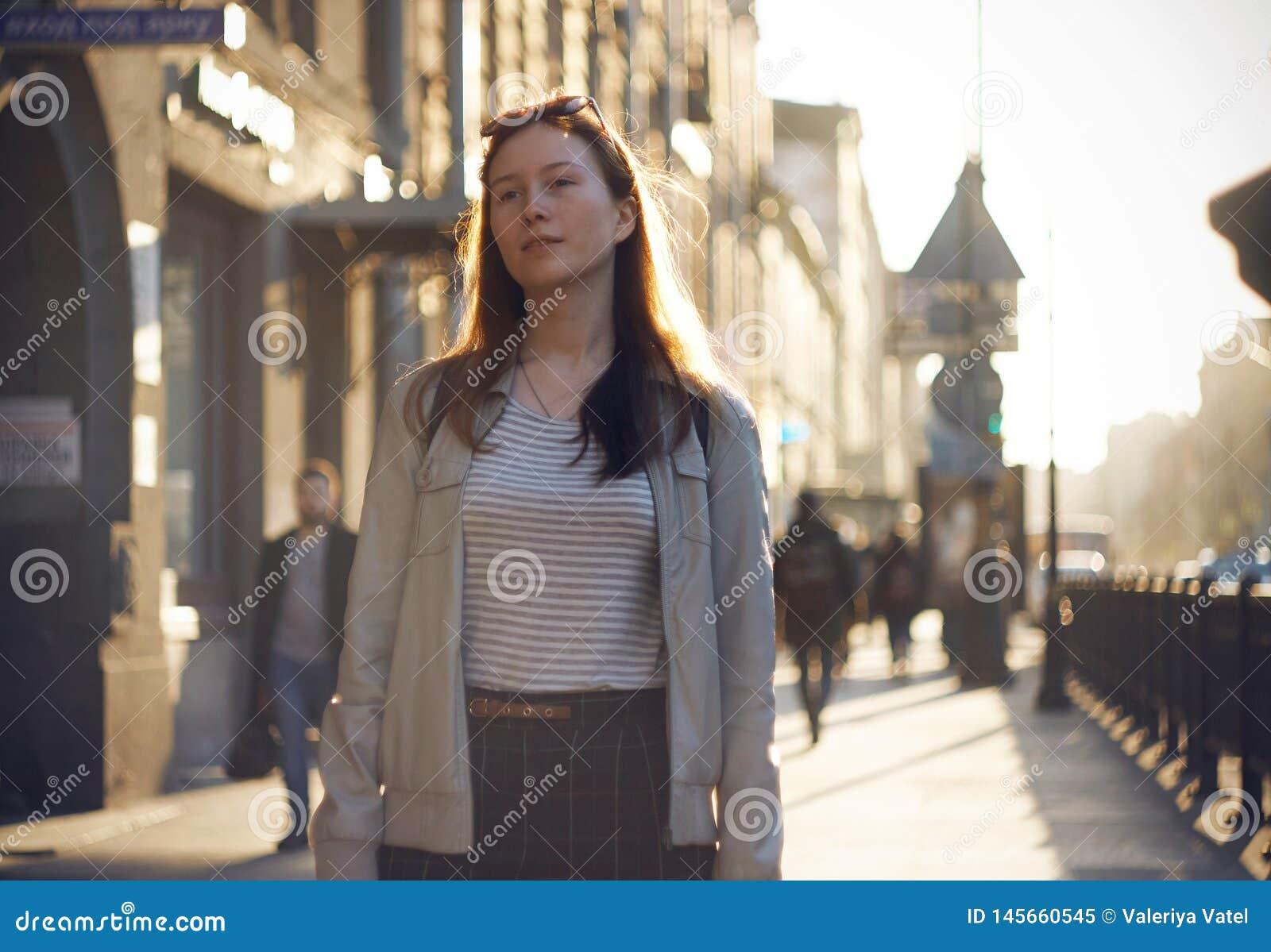 Een roodharig meisje loopt langs de zonovergoten straat