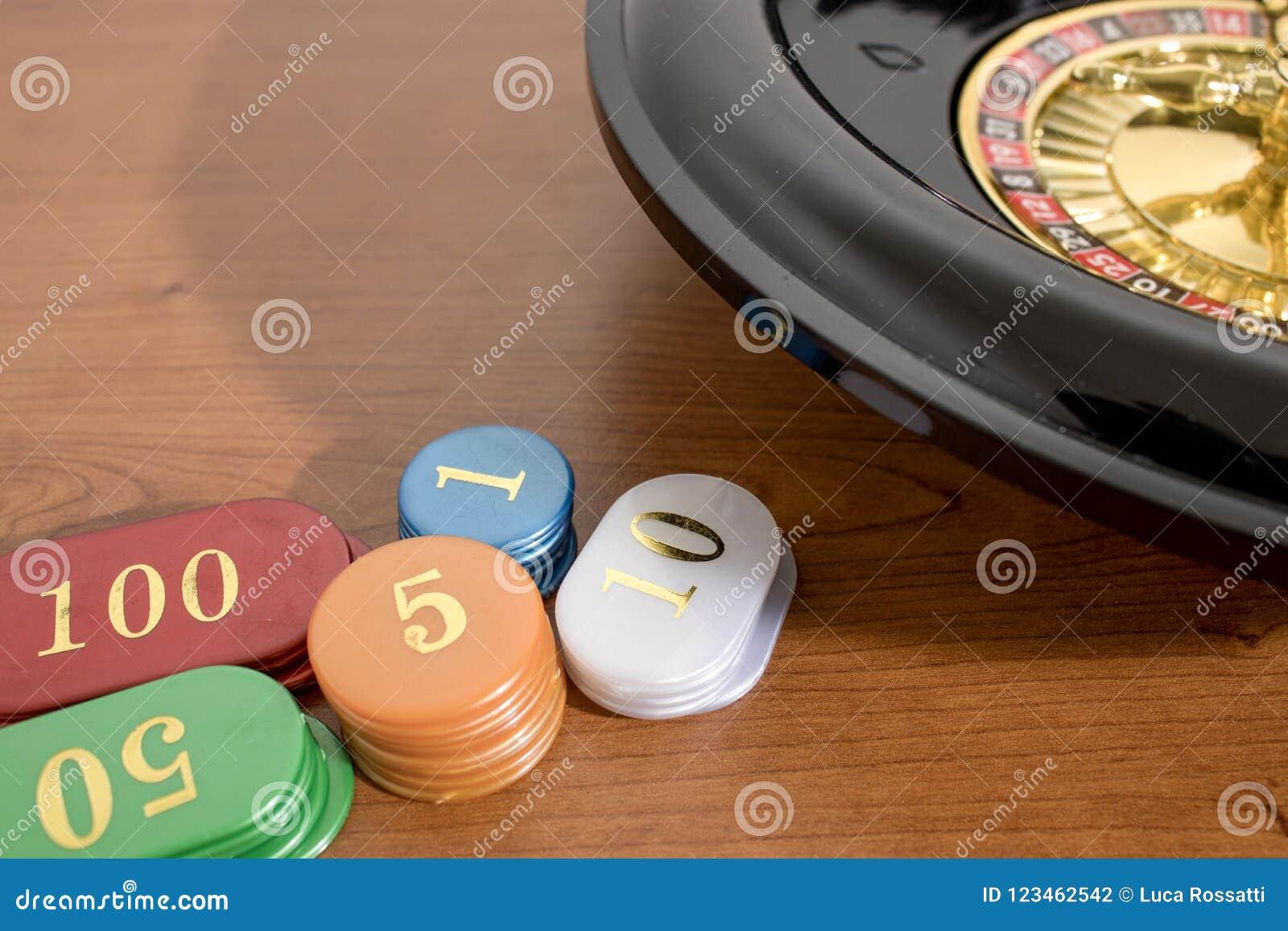Een roulette en gekleurde casinospaanders op een houten lijst