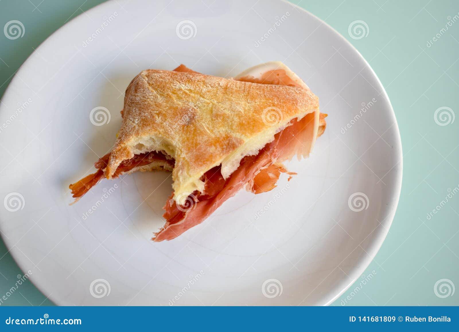 Een sandwich van de serranoham met een grote beet bij een hoek op een witte plaat op een kristallijst