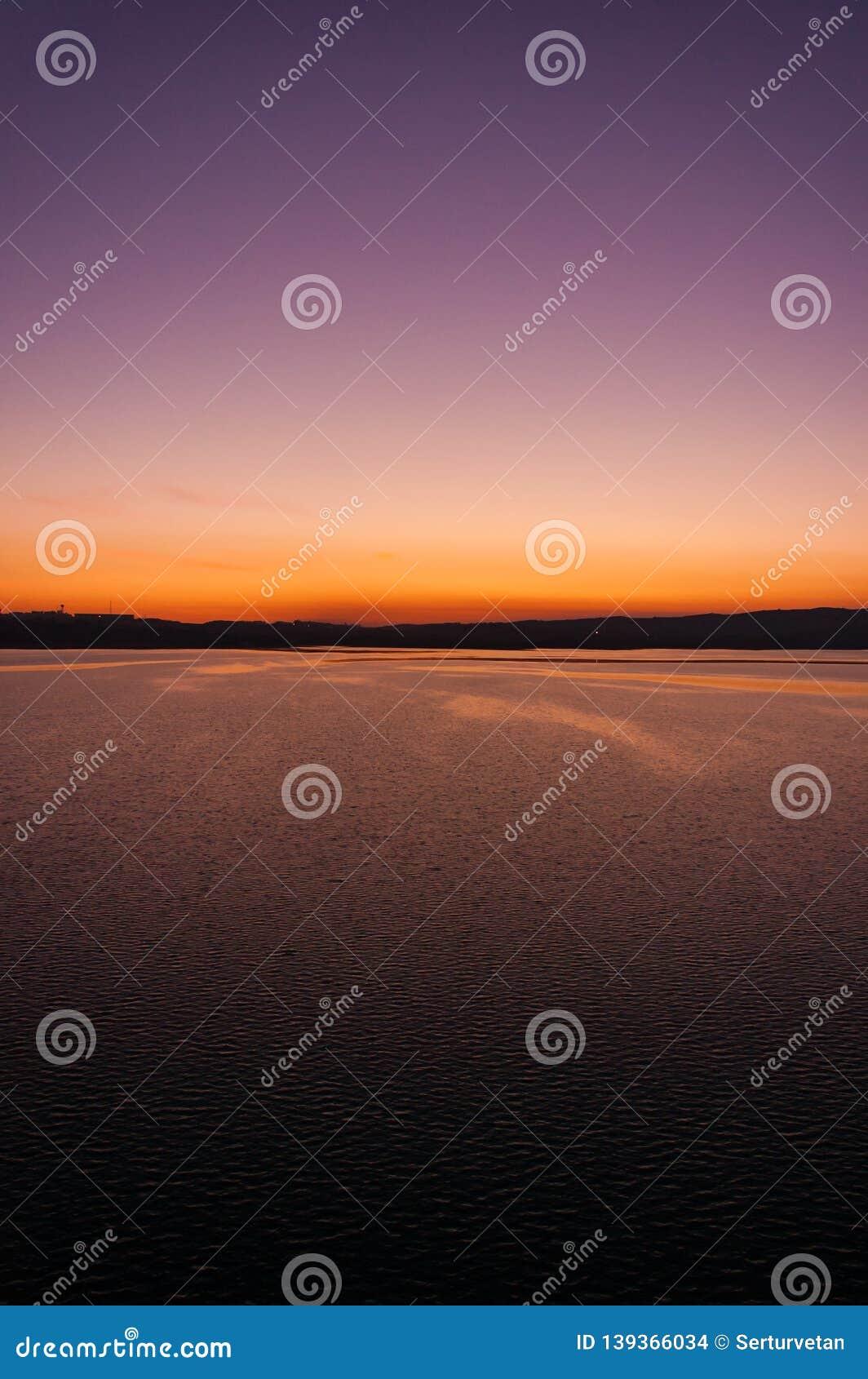 Een schitterend kleur en een contrast over het meer bij zonsondergang Verticaal kader