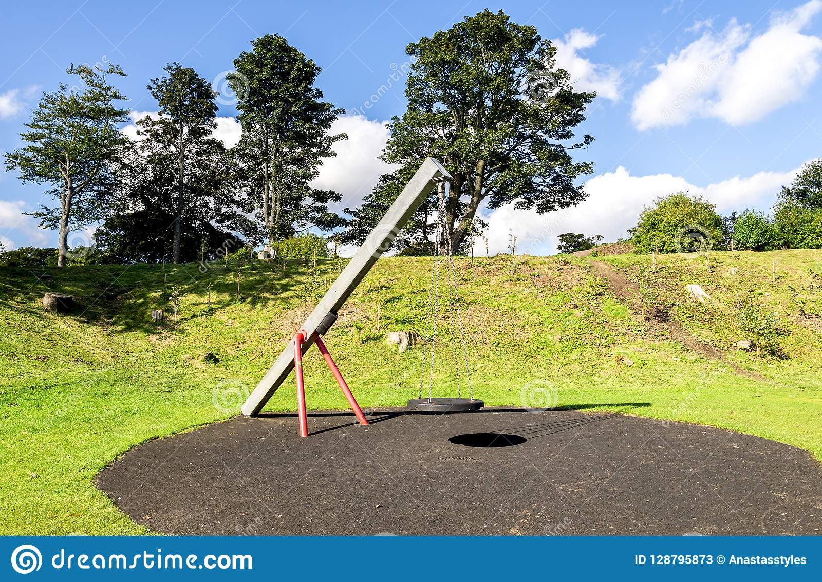 Een schommeling met een rubber ronde zetel die op vier kettingen in Duthie-parkspeelplaats hangen, Aberdeen