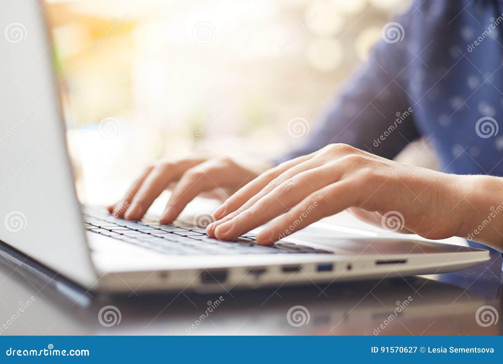 Een schot van vrouwen` s handen die op toetsenbord typen terwijl het babbelen met vrienden die computerlaptop zitting gebruiken b