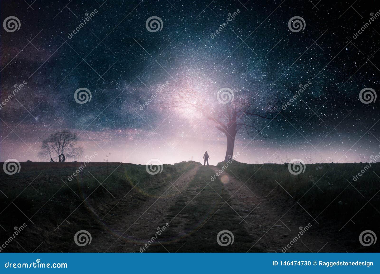 Een science fictionconcept Een geheimzinnig cijfer met een kap dat tegen een helder licht door een dode boom op een weg van het l