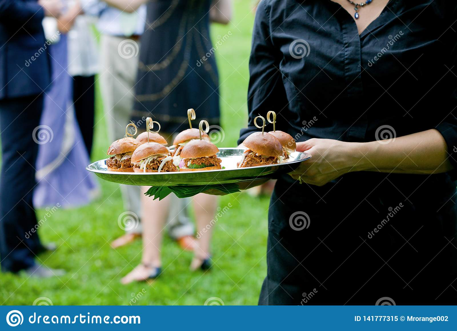 Een server die een dienbladhoogtepunt van mini getrokken varkensvleessandwiches houden tijdens een gerichte gebeurtenis