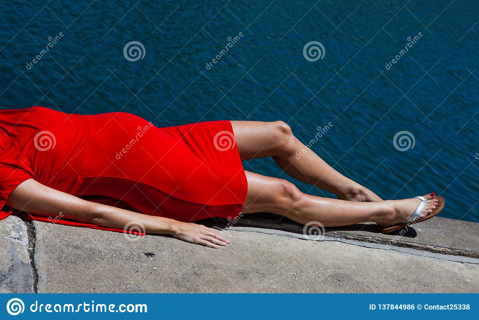 Een slanke tengere zwangere damesbuik het liggen in rode kleding