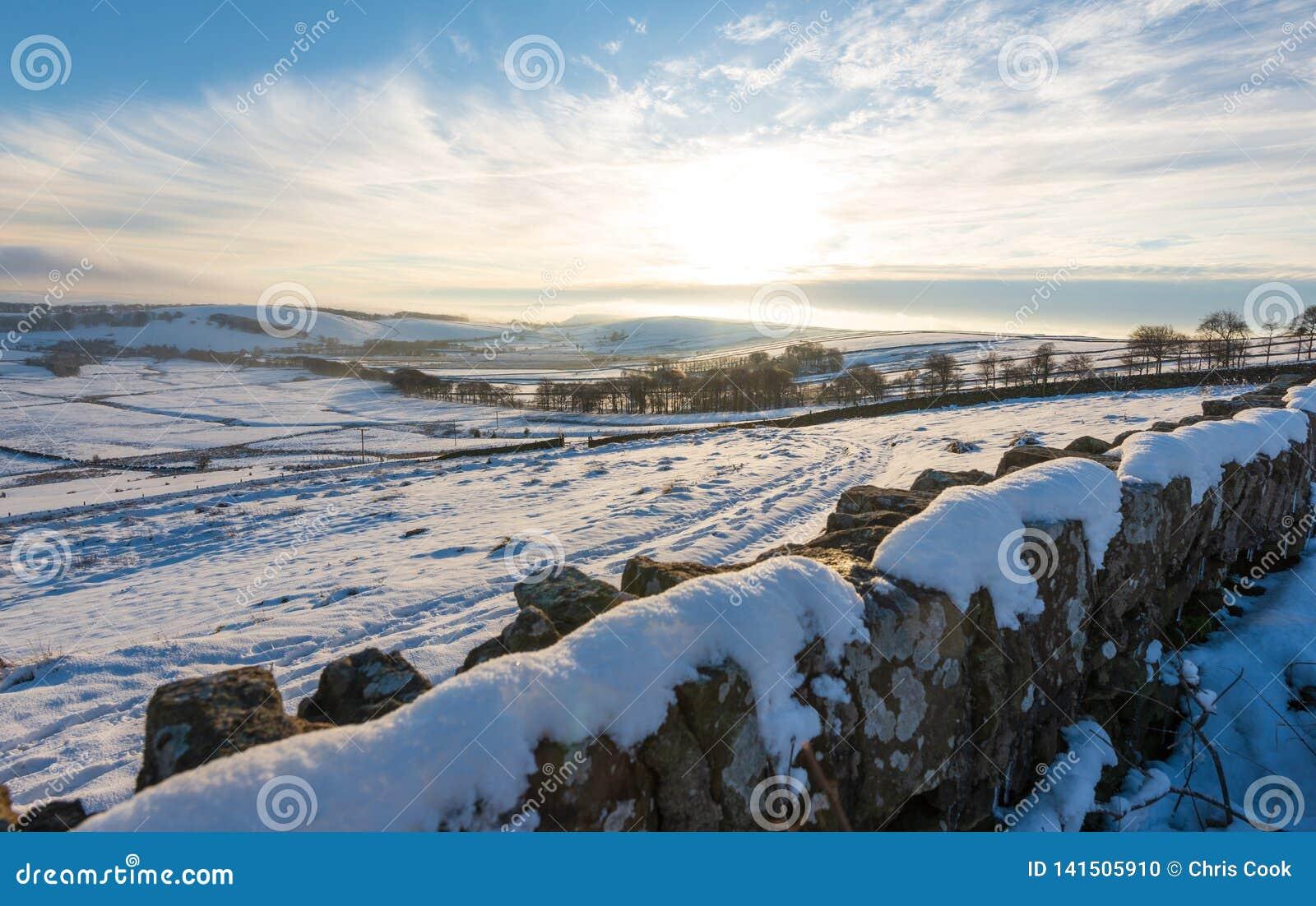Een sneeuwmuurlijnen de mening van een mooie koude zonsondergang in het Piekdistrict