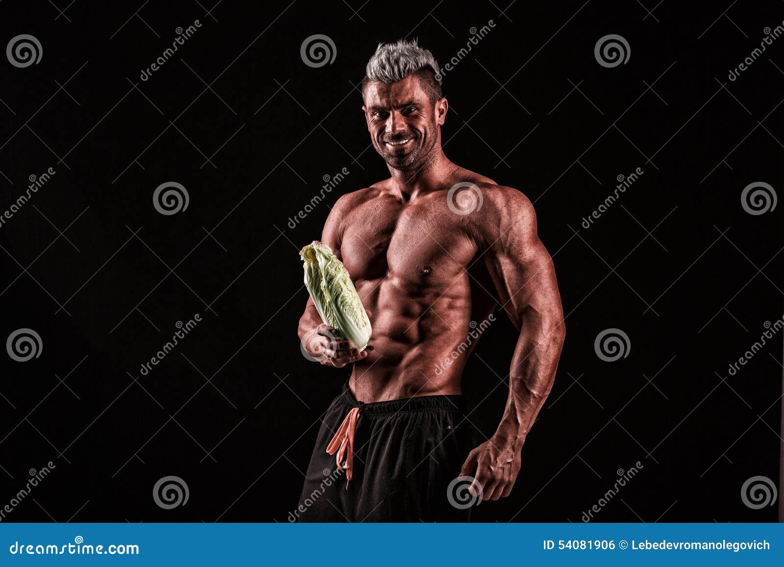 Een spierkerel en een verse groente, gevormde buik