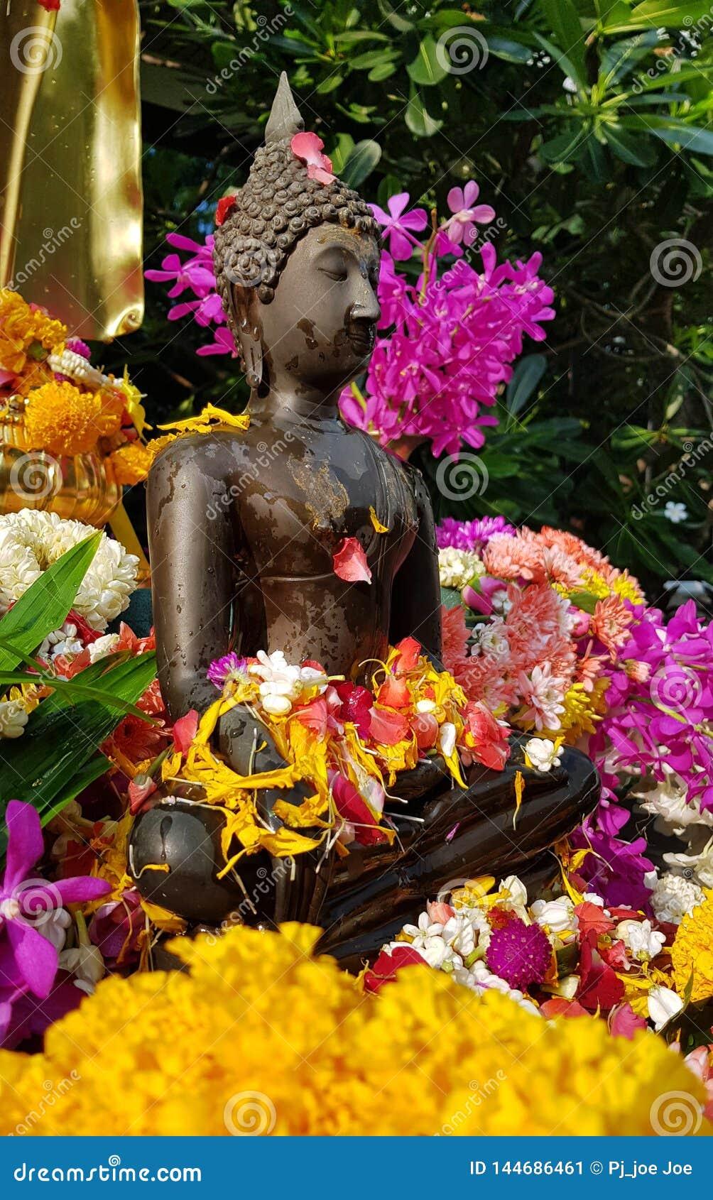 Een standbeeld van brons klein Boedha bij de tempel met natte gele rode bloembloemkronen voor Songkran-festival