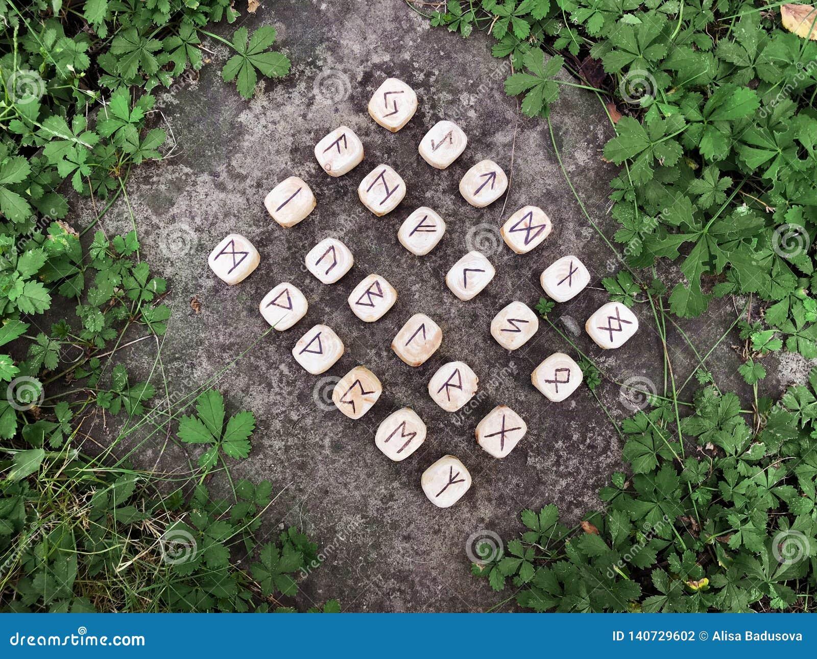 Een stapel houten runen bij bos Houten runen ligt op een rotsachtergrond in het groene gras De runen worden gesneden van houten