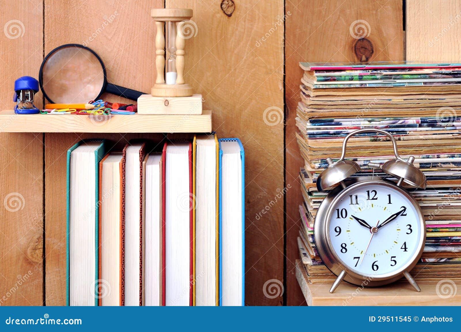 Een stapel van oude tijdschrift, klok, boeken en kantoorbehoeften