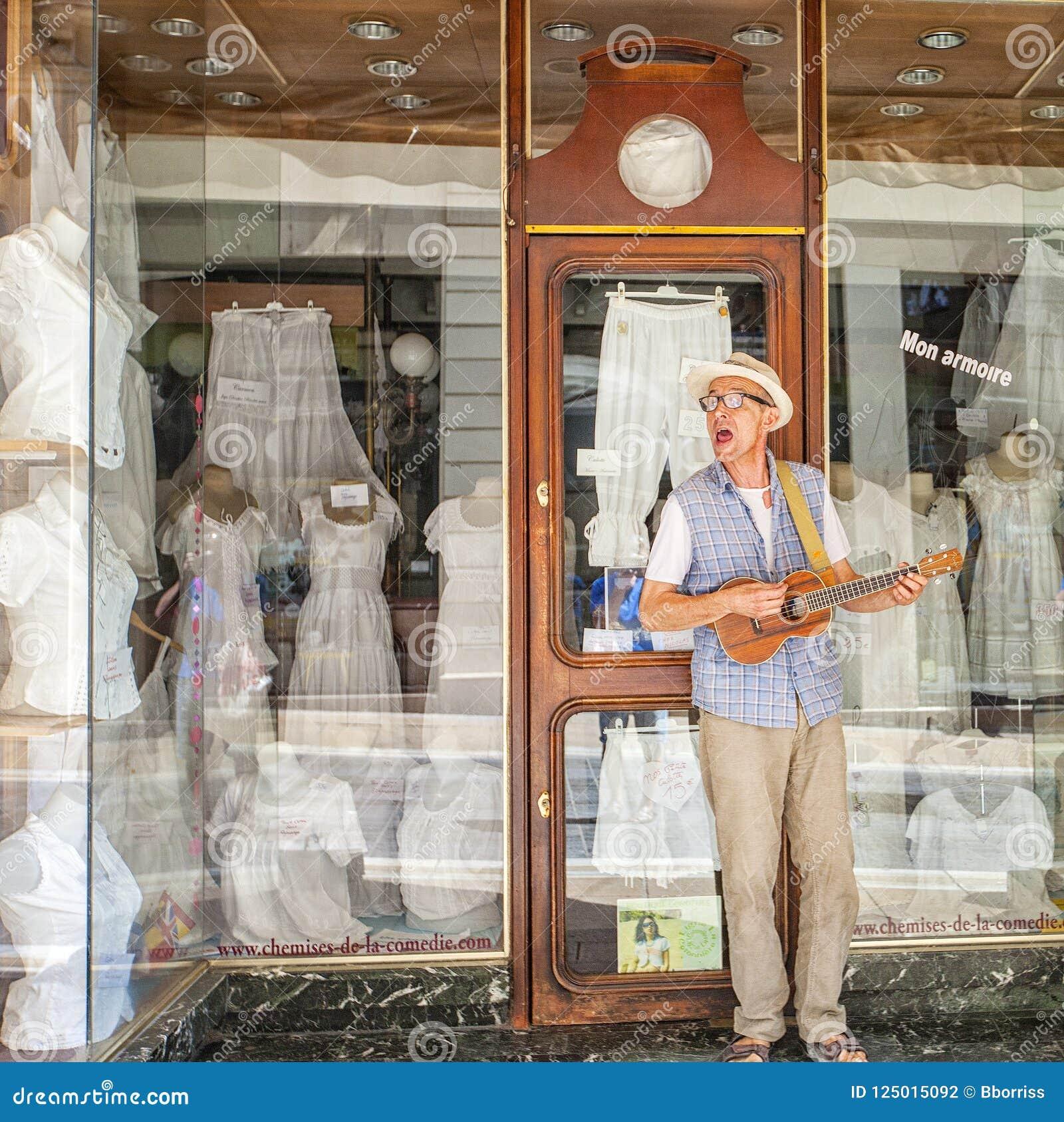 Een straatmusicus die en in kostuum in de stad van Montpellier, Frankrijk spelen zingen