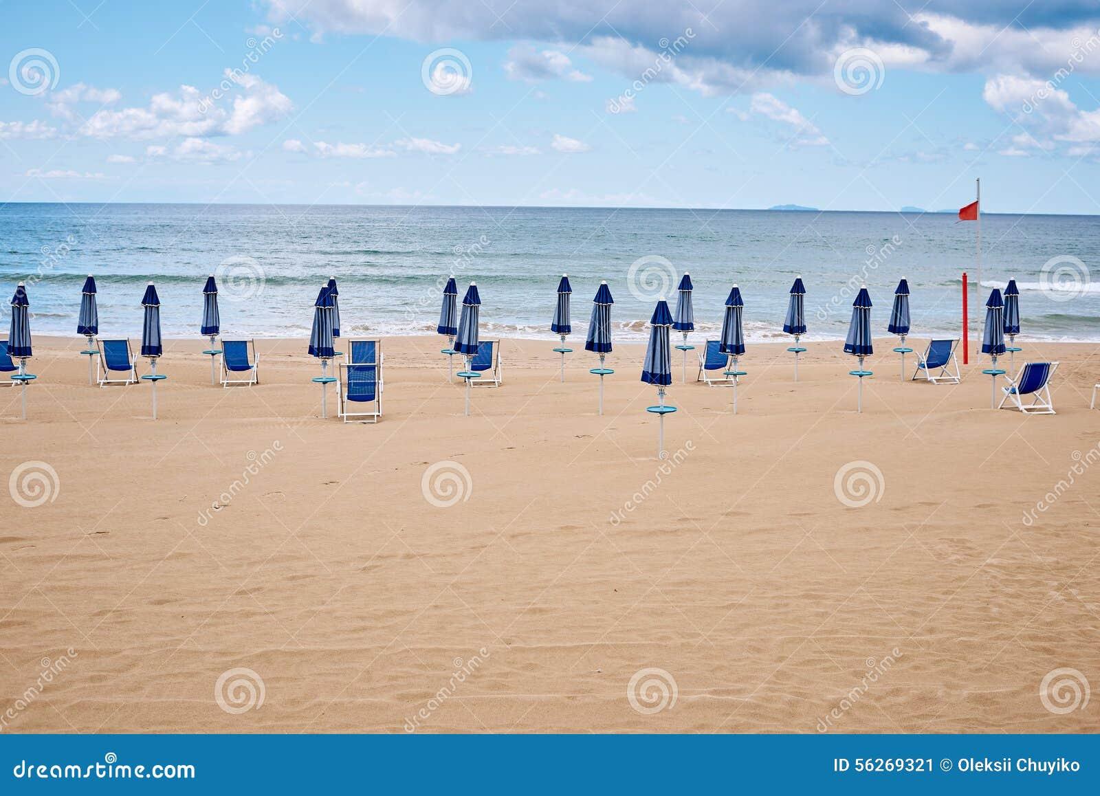 Een strand met paraplu s en zonbedden op kust