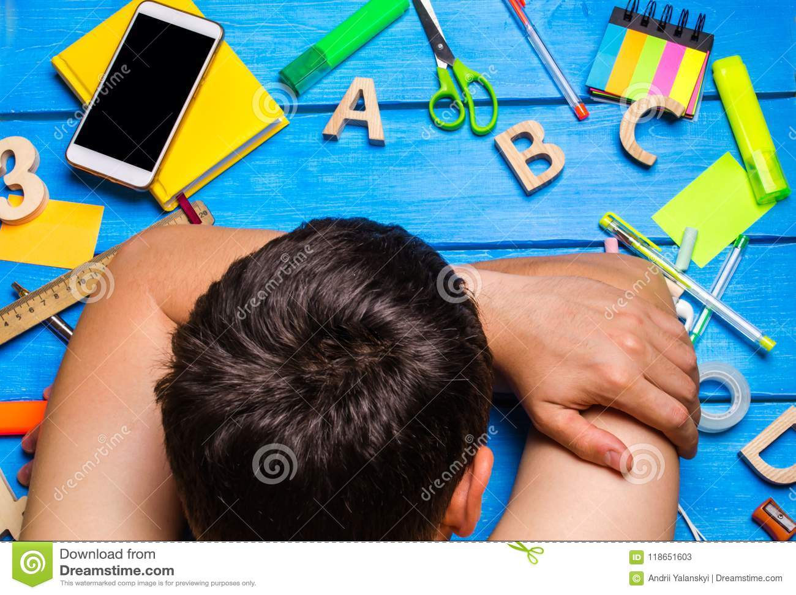Een student is in slaap in de werkplaats, knoeit creatief De student is lui en wil niet leren De kerel is vermoeid en in slaap